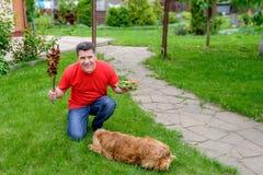 L'homme supérieur s'assied sur l'herbe avec le chiche-kebab et un plat avec des légumes Photos libres de droits