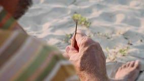 L'homme supérieur s'assied sur la plage et cannelure de fabrication à la main, plan rapproché clips vidéos