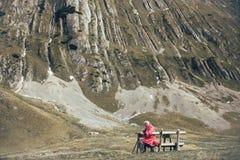 L'homme supérieur s'assied sur le banc dans la montagne Photographie stock libre de droits