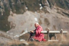 L'homme supérieur s'assied sur le banc dans la montagne Images libres de droits