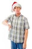 L'homme supérieur utilisant le chapeau de Santa et le faisant manie maladroitement en bas du geste Images stock