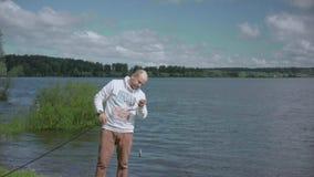 L'homme sur la pêche Repos sur le lac banque de vidéos