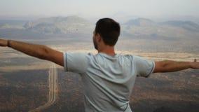 L'homme sur le dessus de la montagne remet aux côtés et dépeint le vol banque de vidéos