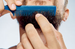 L'homme sur le fond d'isolement par blanc peigne la barbe photographie stock