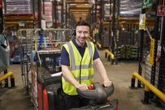 L'homme sur le tracteur de remorquage à l'entrepôt de distribution regarde à l'appareil-photo photographie stock libre de droits