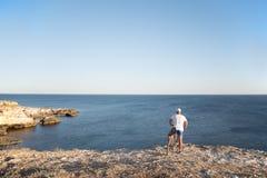 L'homme sur le vélo sur le bord de la mer Image stock