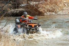 L'homme sur le vélo de quadruple monte sur la rivière avec de l'eau de éclaboussement Photographie stock