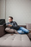 L'homme sur un sofa avec l'ordinateur portable Photographie stock