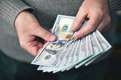 L'homme tenant des billets de banque des dollars d'argent Photo stock