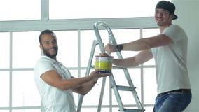 L'homme tenant une peinture peut tandis que sa position d'ami clips vidéos