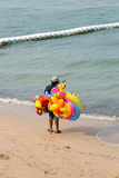 L'homme thaïlandais vend les jouets gonflables à la plage Images stock