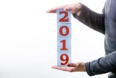 L'homme tient des cubes avec les numéros 2019 photographie stock libre de droits