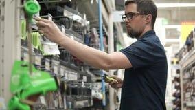 L'homme tient deux pelles en métal dans des mains dans un département de magasin pour des constructeurs banque de vidéos