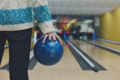 L'homme tient la boule à la ruelle de bowling, image cultivée photographie stock