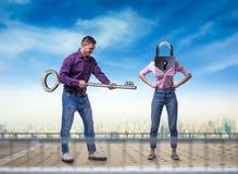 L'homme tient la clé, femme avec le trou de la serrure au lieu de la tête photos libres de droits