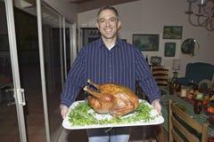 L'homme tient la dinde cuite devant une table mise pour le dîner de thanksgiving dans Ojai, la Californie Photo libre de droits