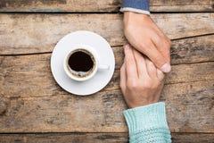 L'homme tient la main de la femme avec la tasse de café Photo libre de droits
