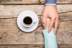 L'homme tient la main de la femme près d'une tasse de café Photo stock
