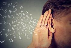 L'homme tient la main près de l'oreille écoute soigneusement des lettres d'alphabet volant dedans Image stock