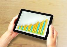 L'homme tient le comprimé numérique avec le graphique de gestion sur un écran Images libres de droits
