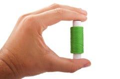 L'homme tient le fil vert de bobine Image stock