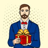L'homme tient le grand boîte-cadeau Vecteur dans le rétro style comique d'art de bruit Un type avec Noël ou le cadeau d'anniversa Photos libres de droits
