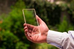 L'homme tient le téléphone intelligent transparent futuriste à un arrière-plan brouillé par vert Photo stock