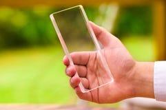 L'homme tient le téléphone intelligent transparent futuriste dans sa main Photographie stock
