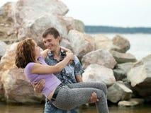L'homme tient son épouse sur des mains dehors photo libre de droits
