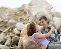 L'homme tient son épouse sur des mains dehors photo stock