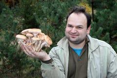 L'homme tient sur sa paume beaucoup de champignons, connus sous le nom de champignon de miel photo libre de droits