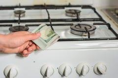 L'homme tient un connaissement dans des ses mains dans un signe de la hausse du prix du gaz naturel pr?s de la cuisini?re ? gaz photos stock