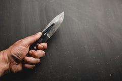 l'homme tient un couteau tactique dans sa main images stock