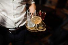 L'homme tient un plateau avec un glasse vide et avec le mélange aigre et le negroni de deux cocktails alcooliques Image stock