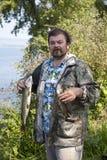 L'homme tient un poisson dans des ses mains Photos stock