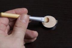 L'homme tient une brosse pour appliquer des cosmétiques Il est abaissé par une astuce dans un récipient rond avec une barre de mi photos stock