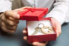 L'homme tient une maison miniature dans un boîte-cadeau Logement comme cadeau Gagnez un appartement dans la loterie Pour hériter  photographie stock libre de droits