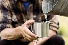 L'homme tient une tasse en acier et une eau de puits verse d'un seau photographie stock