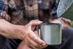 L'homme tient une tasse en acier et une eau de puits verse d'un seau photographie stock libre de droits