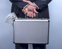 L'homme tient une valise avec l'argent derrière le dos Photos stock