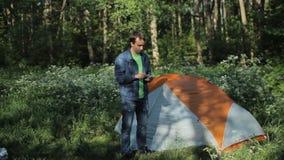 L'homme touche le téléphone à côté de la tente Début de la matinée dans la forêt banque de vidéos
