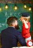 L'homme a tourné embrasser de retour le garçon blond dans le chapeau d'obtention du diplôme Enfant fatigué frottant ses yeux Adul photo stock
