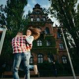 L'homme tourne activement autour de sa belle amie avec le sourire avec du charme tout en dansant dans la rue Photos stock