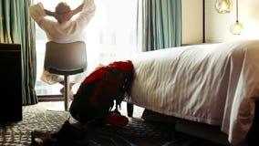 L'homme tourne se reposer sur un tabouret tournant dans sa chambre d'hôtel après la prise d'une douche clips vidéos