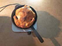 L'homme tourne un poulet frit dans une casserole sur une plaque chauffante Cuisson du poulet frit photos stock