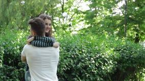 L'homme tourne une fille sur des mains en parc banque de vidéos