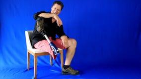 L'homme très bien disposé entre et s'assied dans la chaise, salue et joue avec la prothèse