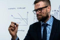 L'homme trace les diverses échelles de croissance, perspectives calculatrices pour le succe Image stock