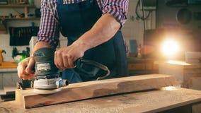 L'homme travaille avec la machine de polissage sur un morceau en bois banque de vidéos