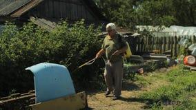 L'homme travaille avec le jet de jardin dans le domaine près de la maison banque de vidéos